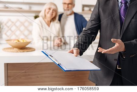 Think about your health today. Confident experienced skilled social security advisor working and presenting contract while the aged couple of clients sitting in the background