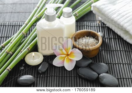 Spa setting with candle , frangipani,towel ,stones ,grove on mat