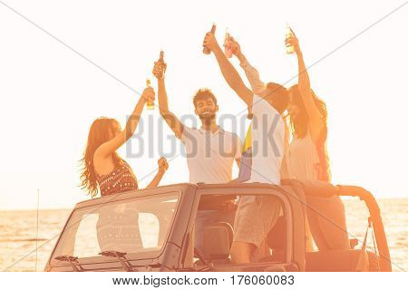 Five young people having fun in convertible car at the beach at sunset. They are wearing summer clothes, hats, and sunglasses and drinking alcoholic drinks.