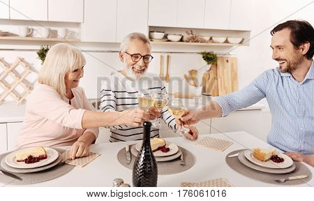 Raising our glasses for happiness. Cute upbeat pleasant aged couple having dinner and celebrating holiday with their mature son while raising glasses full of champagne