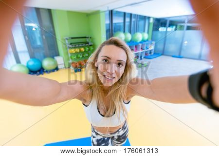 sport woman smile at camera self picture at gym, young girl picture herself exercising fitness center.