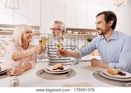 With best wishes to my parents. Positive happy mature man having dinner and enjoying holiday with his aged parents while raising glasses full of champagne and smiling
