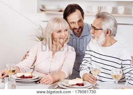 Expressing love to my parents. Happy delighted mindful man having dinner and enjoying time with his senior parents while hugging them