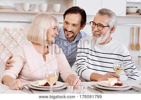 Thanking my parents for everything . Smiling careful handsome man having dinner and enjoying time with his senior parents while expressing love to them