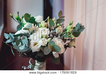 luxury bridal bouquet made of white roses and carnation on a window sill