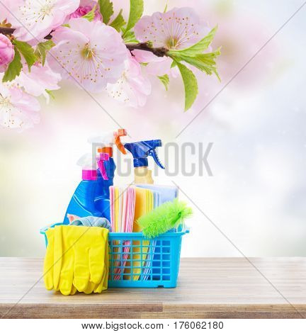 Spring cleaning concept - colorful spays and rubbers on wooden table with spring background