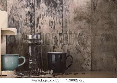 Cup of coffee and beans on old wooden table.