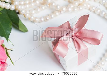 Gift box with pink ribbon with pearl jewellery on white table