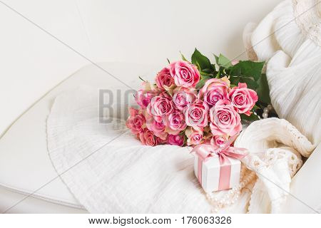Female dress and jewellery with freah roses bouquet and gift box on chair, place for copy space
