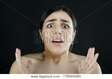 Portrait of a swarthy shocked woman on a black background