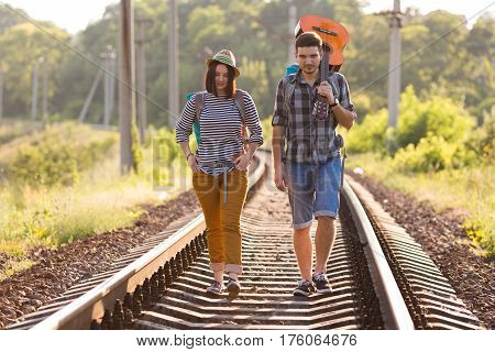 Two jolly Hikers Man and Girl in casual Travel Clothing with Backpacks and Guitar walking along Railroad with back light Sun and Forest on Background