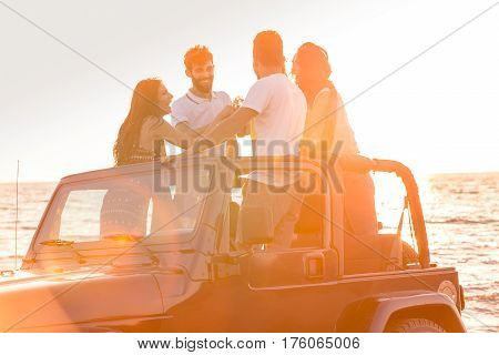 Group of young people having fun in convertible car at the beach at sunset. They are wearing summer clothes, hats, and sunglasses and drinking alcoholic drinks.