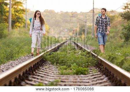 Two jolly Hikers Man and Girl in casual Travel Clothing with Backpacks walking along old Country Railroad with back light Sun and Forest on Background