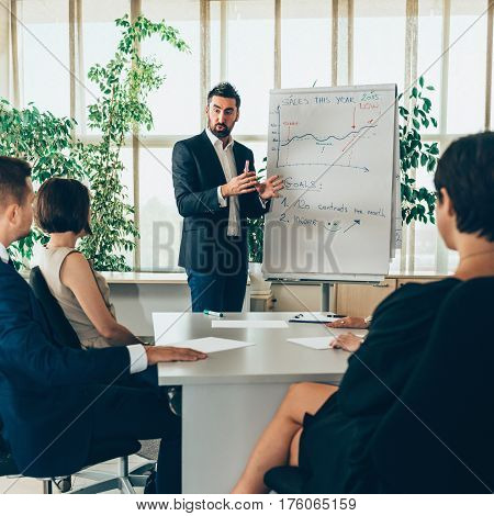 Business presentation in office Male standing and talking in front of flipchart