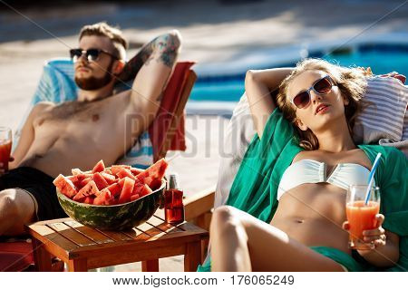 Friends sunbathing, drinking cocktails, lying on chaises near swimming pool. Copy space.