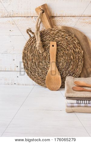 Wood round cutting board rattan coaster stack of linen kitchen towels spoons on white plank wood background Provence style kinfolk