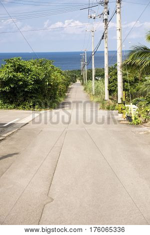 Country road leading to a sea beside telegraph poles in Ishigaki island