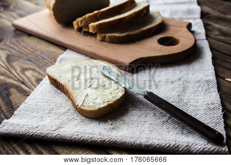 a sliced bread and spread butter by knife