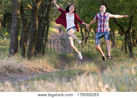 Happy Couple Man and Woman running and jumping holding Hands on Forest Trail in sporty or travel clothing Laughing Faces