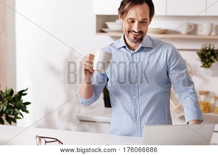 I prefer freelancing job. Smiling glad involved man standing at home and drinking cup of tea while enjoying freelance responsibilities and using laptop