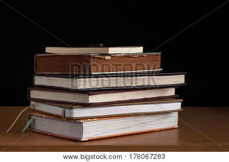Old books that are stacked on a wooden table.