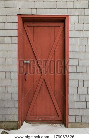 Oxblood red barn style X door on cedar shakes shingles background. Snow on the ground.