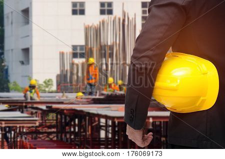 double exposure of businessman hold in hand yellow safety helmet  industrial concept on blurred construction site workers background, color tone effect.