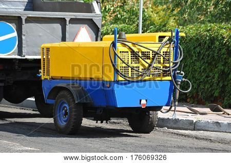 Jackhammer machine with compressor on road construction site