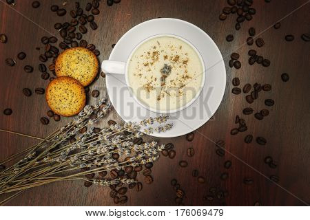 Cup of coffee with milk pussy-willow and dried branches and leaves at white background. Cake on desk