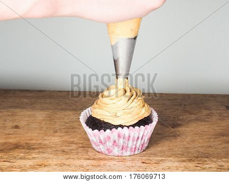 Professional Cake Baker Applying Frosting Onto A Chocolate Cupcake On A Wooden Table