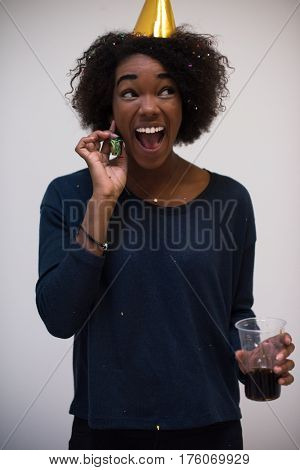 portrait of a young beautiful black woman in party hat blowing in whistle isolated on a white background