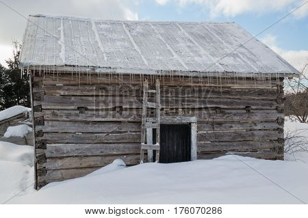 Snowy Old Log Cabin Barn With Icicles