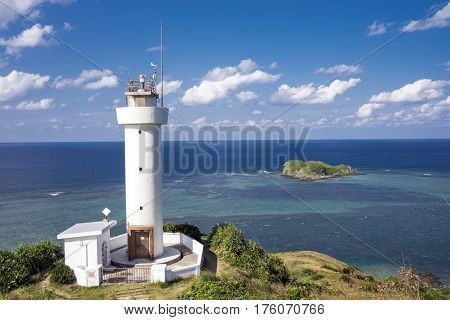 Lighthouse on cape in front of sea under sky in Ishigaki island