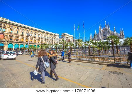 Milan, Italy - March 7, 2017: Famous Milan Dome Cathedral, the Duomo in a blue sky day. Tourists and new palm trees planted in front square Piazza Duomo.