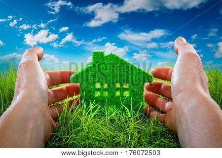 Eco House in green grass protected by the human hands on blue sky background.