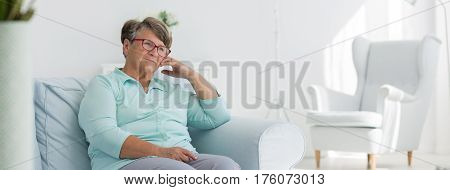 Female elderly person sitting on the armchair