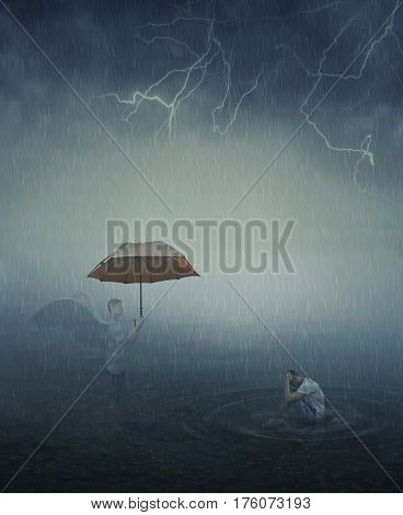 Surrealistic image as lonely stressed man sit in the lake water below the falling rain and his angel try to help him giving an umbrella. Forgiveness spiritual support.