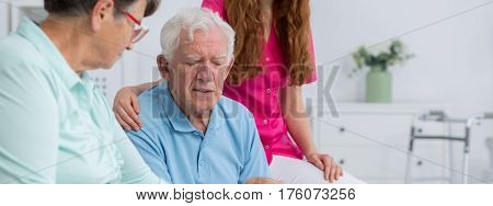 Two thoughtful senior citizens with a nurse