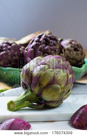 Fresh big Romanesco artichokes green-purple flower heads ready to cook seasonal food