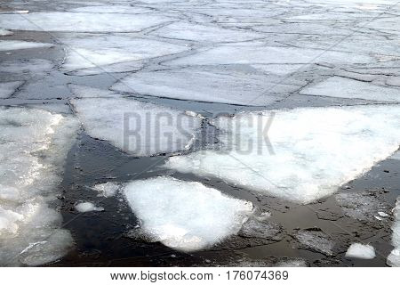 Landscape with melt broken ice floes floating on the river on a spring day close up