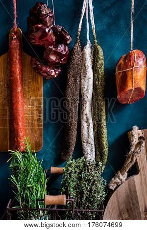 Assortment of sausages Spanish charcuterie wood cutting board fresh garden herbs on dark blue background gourmet