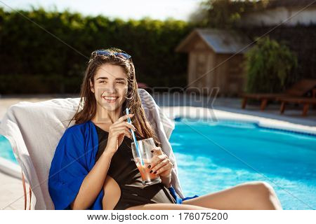 Beautiful brunette girl smiling, drinking cocktail, lying on chaise near swimming pool. Copy space.