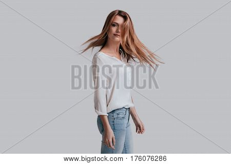 Hair in motion. Attractive young woman with tousled hair looking at camera while standing against grey background