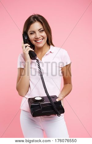 Nice woman in bright casual outfit making phonecalls and smiling looking away isolated on pink