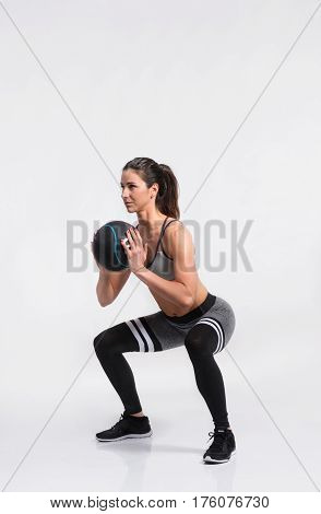 Attractive young fitness woman in sports bra and black leggings holding medicine ball, doing squat. Slim waist, perfect fit female body. Studio shot on gray background.