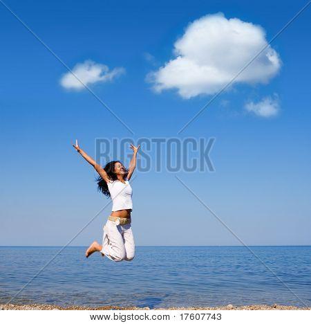 felice giovane donna sta saltando in spiaggia
