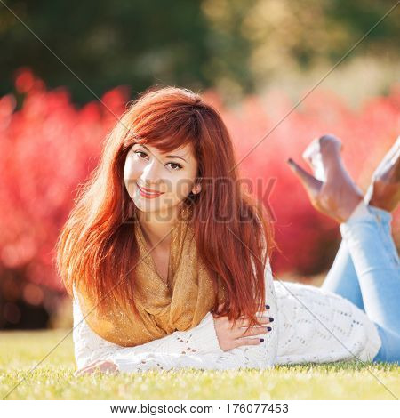 Young pretty woman relaxing in the park. Walk in the park. Beauty nature scene with colorful background, trees and flowers. Healthy outdoor lifestyle. Happy smiling woman relax on green grass