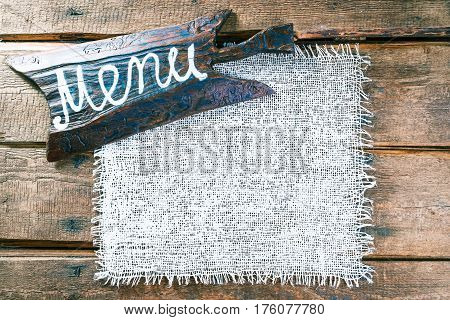 Vertical frame of white burlap on rough pine wood boards. Wooden cutting board with text 'Menu' as title bar. Structured natural style background