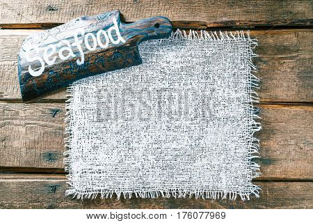 Vertical frame of white burlap on rough pine wood boards. Wooden cutting board with text 'Seafood' as title bar. Structured natural style background