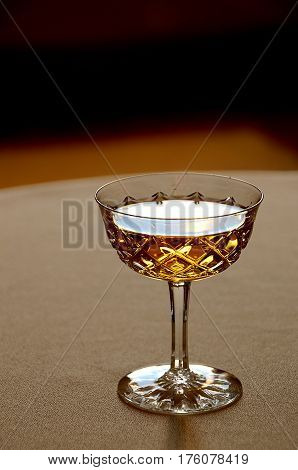 Cut glass. In the foreground on the table in the crystal glass golden liqueur.